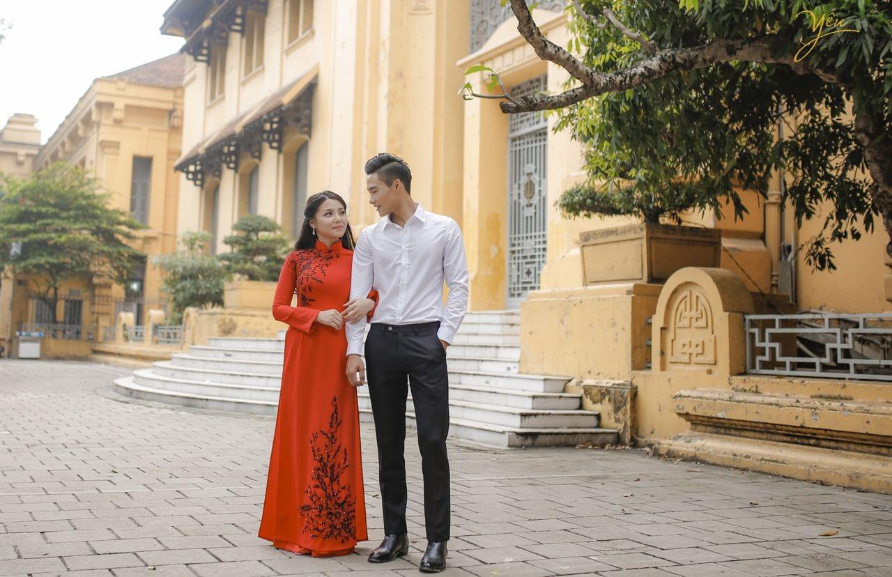 ảnh chụp cưới cô dâu mặc áo dài đỏ nép sát vào chú rể
