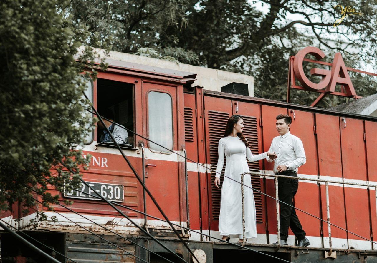 ảnh cưới áo dài trắng chú rể nắm tay cô dâu đi cạnh ga tàu hỏa