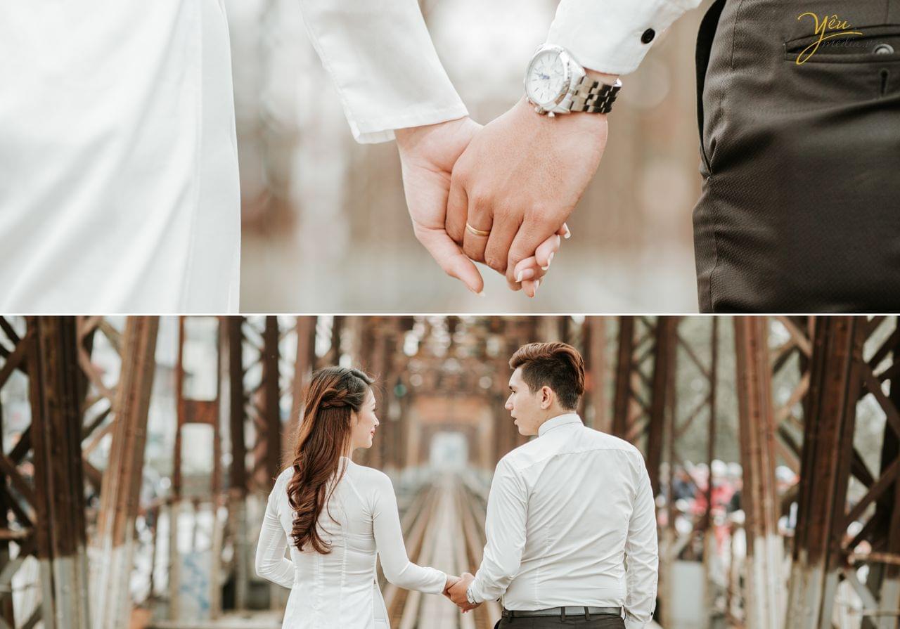 ảnh cưới chụp cô dâu chú rể nắm tay đi trên đường ray cầu long biên