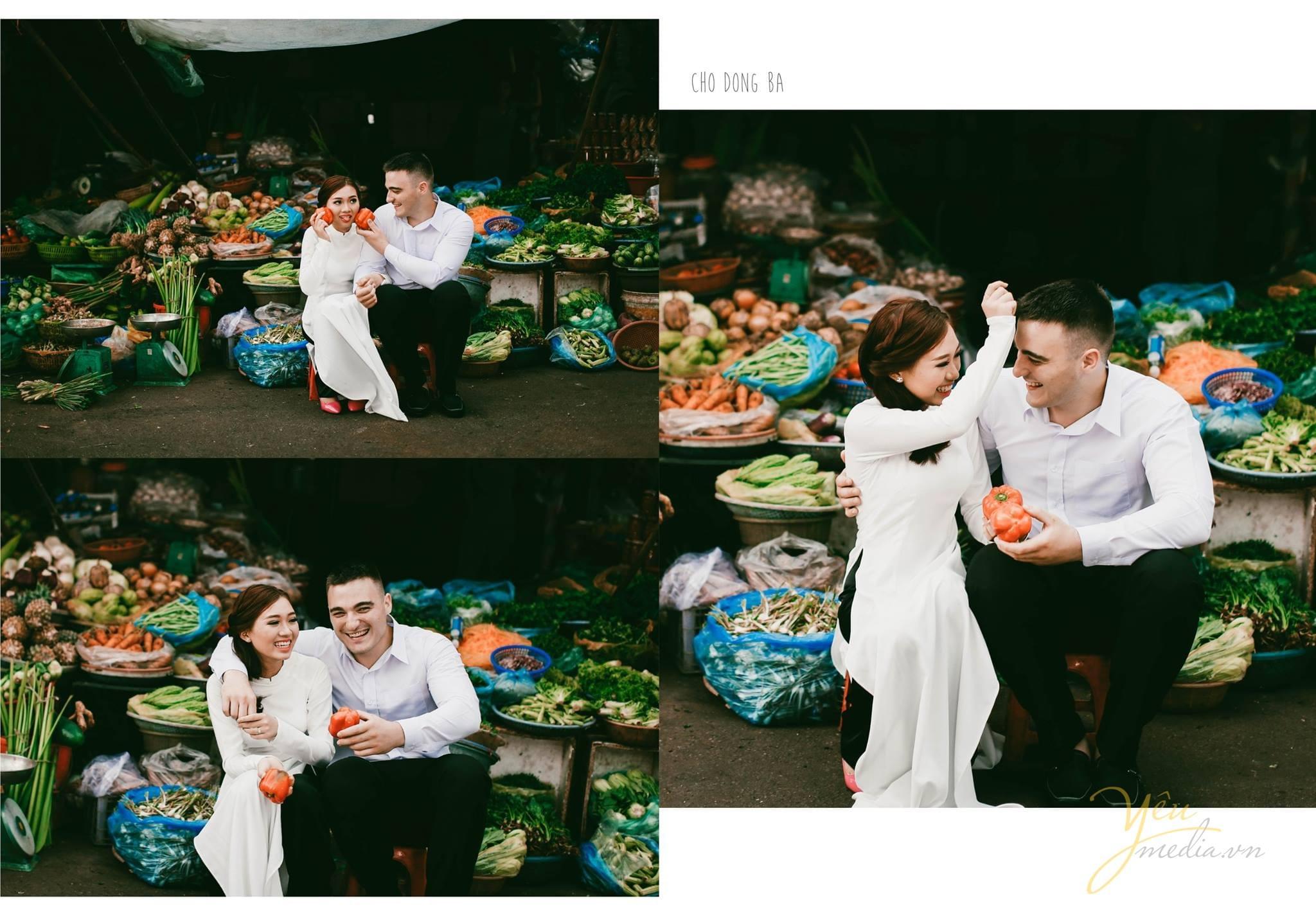 ảnh cưới cô dấu mặc áo dài trắng ngồi với chú rể trong chợ