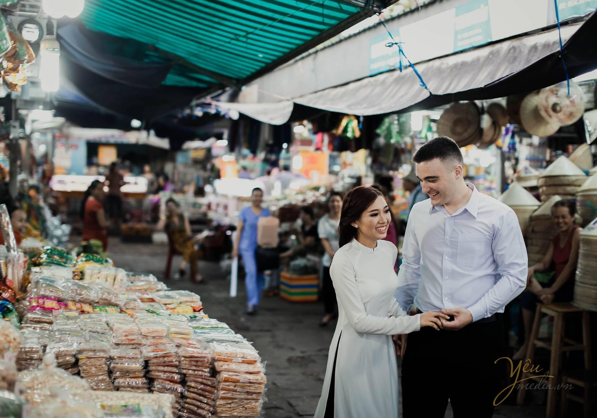 ảnh cưới chụp tại chợ cô dâu chú rể cười nói tự nhiên cạnh hàng bánh kẹo