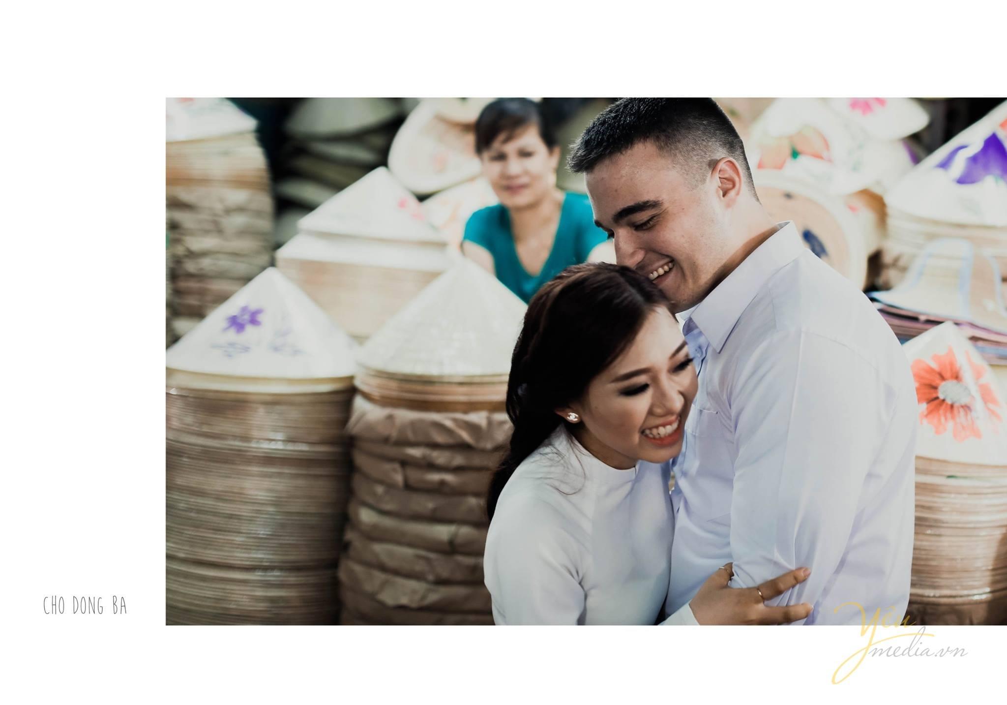 ảnh cưới chụp áo dài trắng cạnh hàng bán nón lá việt Nam