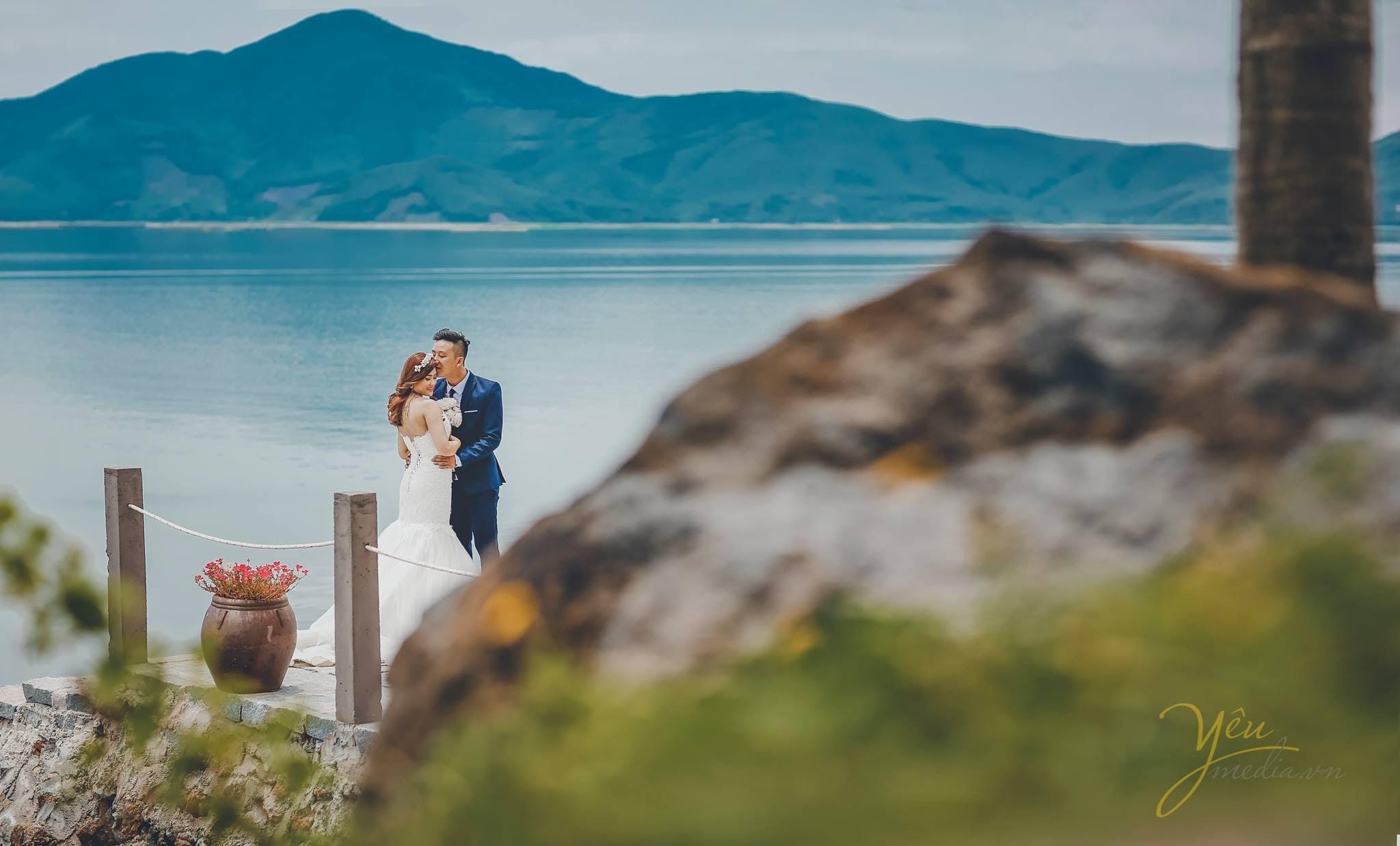 ảnh chụp cô dâu chú rể đứng trên cầu hôn nhau