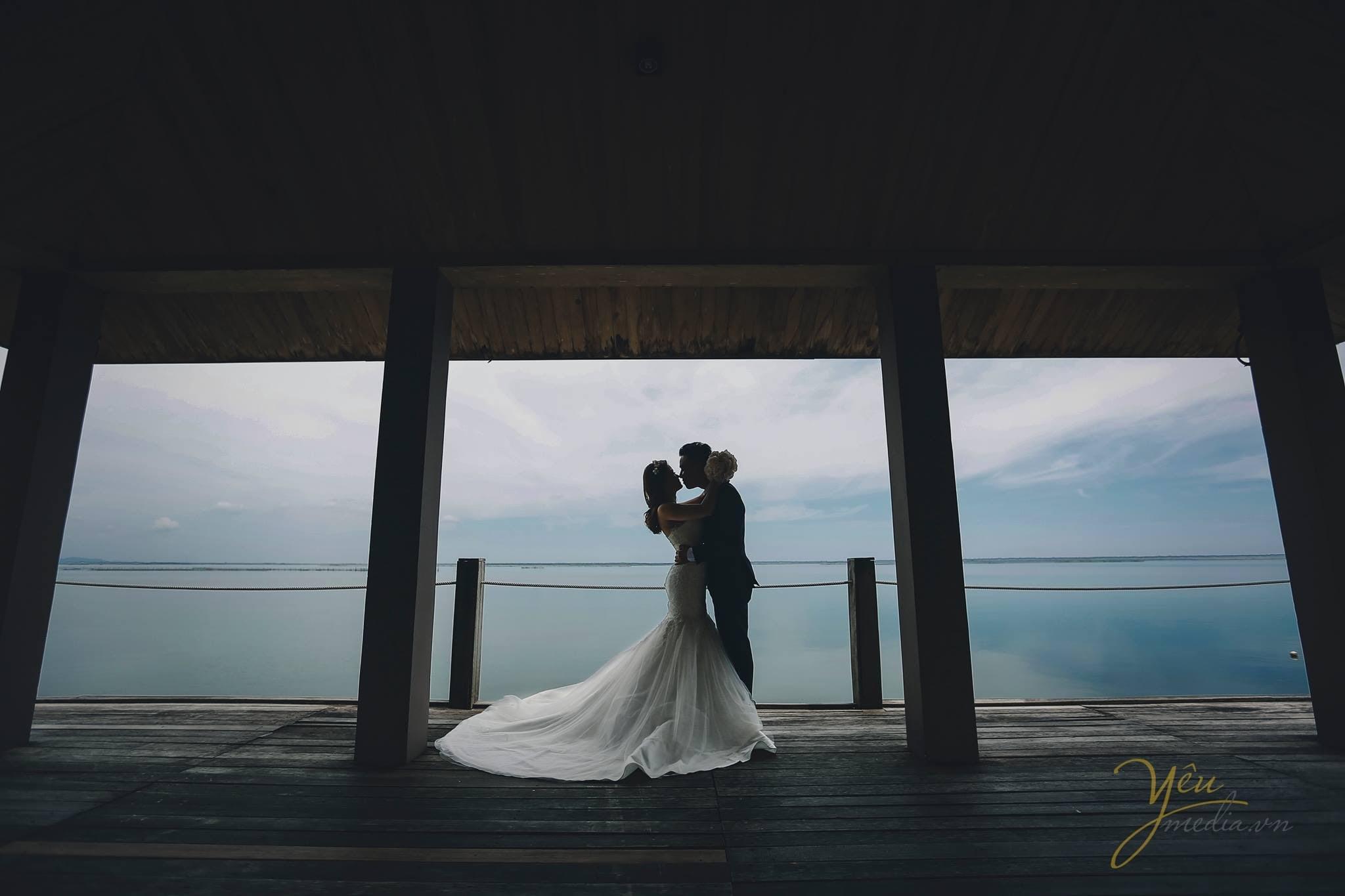 ảnh chụp cô dâu chú rể hôn nhau trên cầu nhìn ra hồ