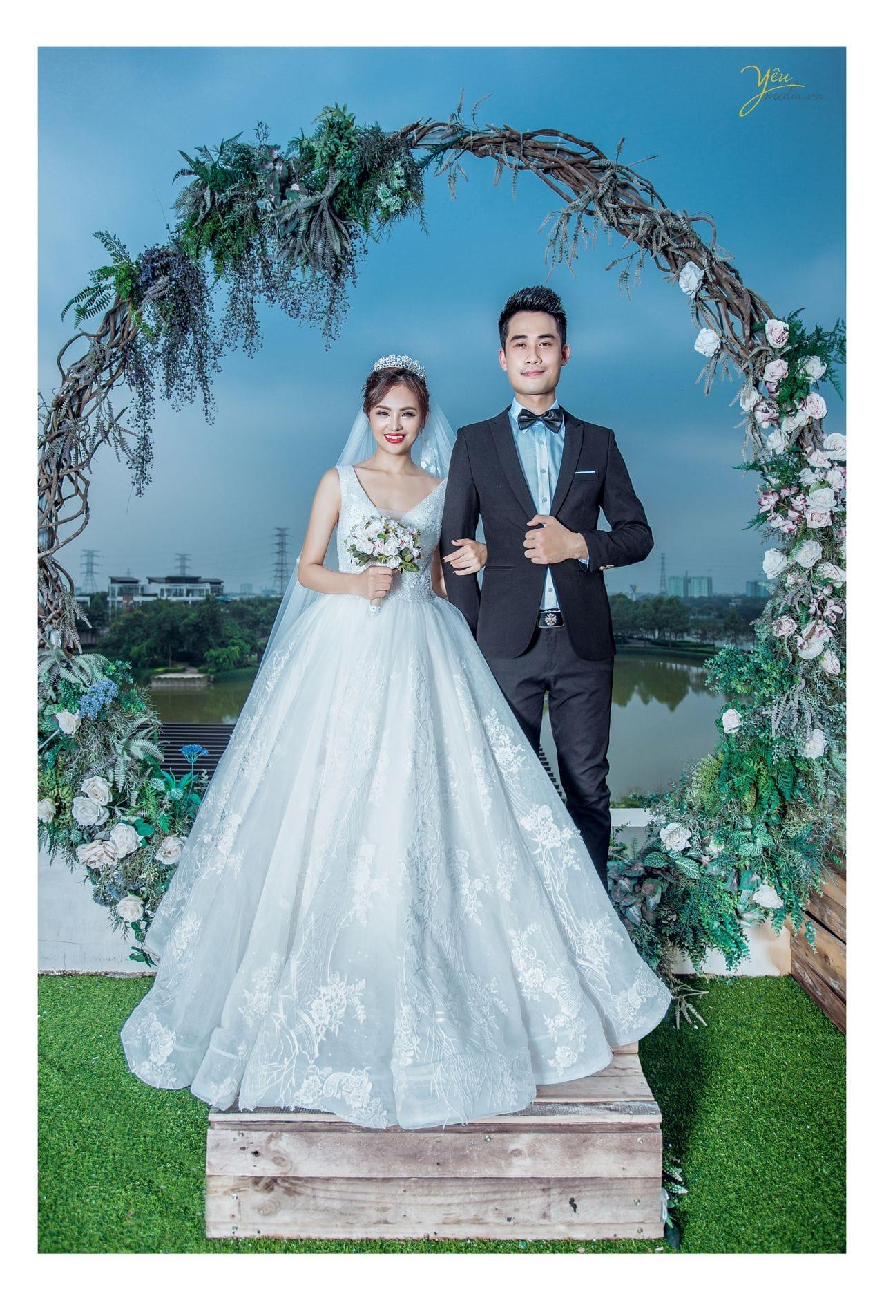 ảnh chụp cô dâu chú rể đứng trước cổng hoa