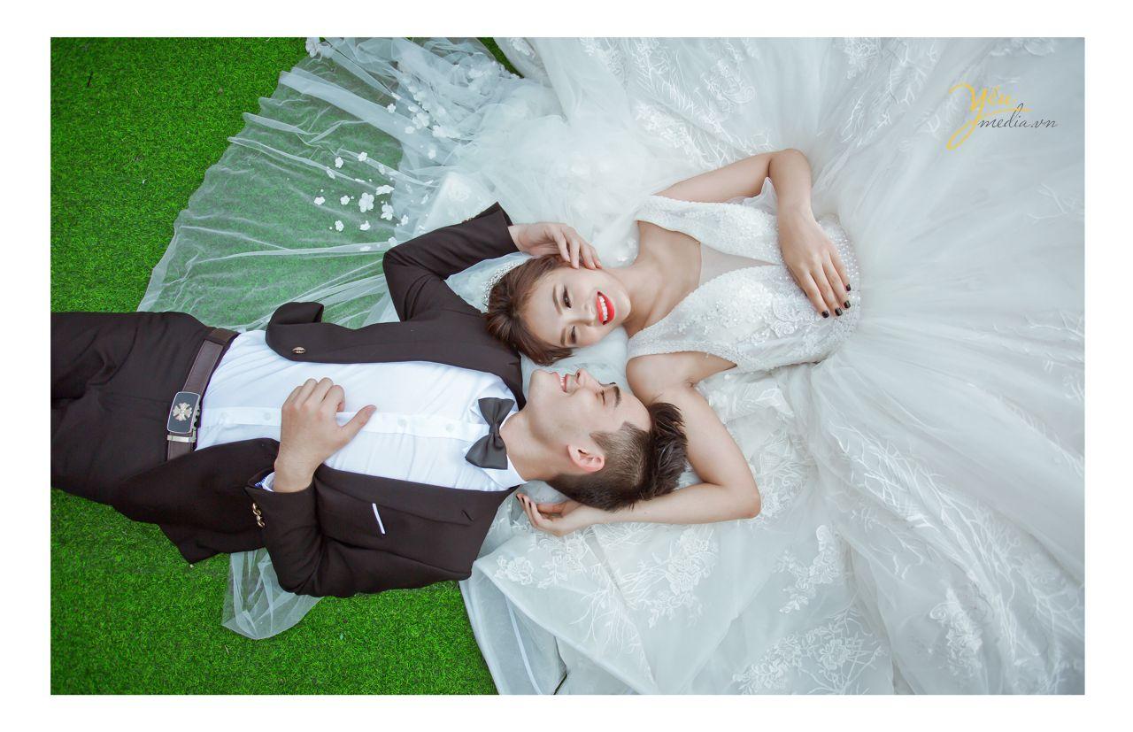 ảnh chụp cô dâu chú rể nằm ngược đầu nhau trên váy cưới