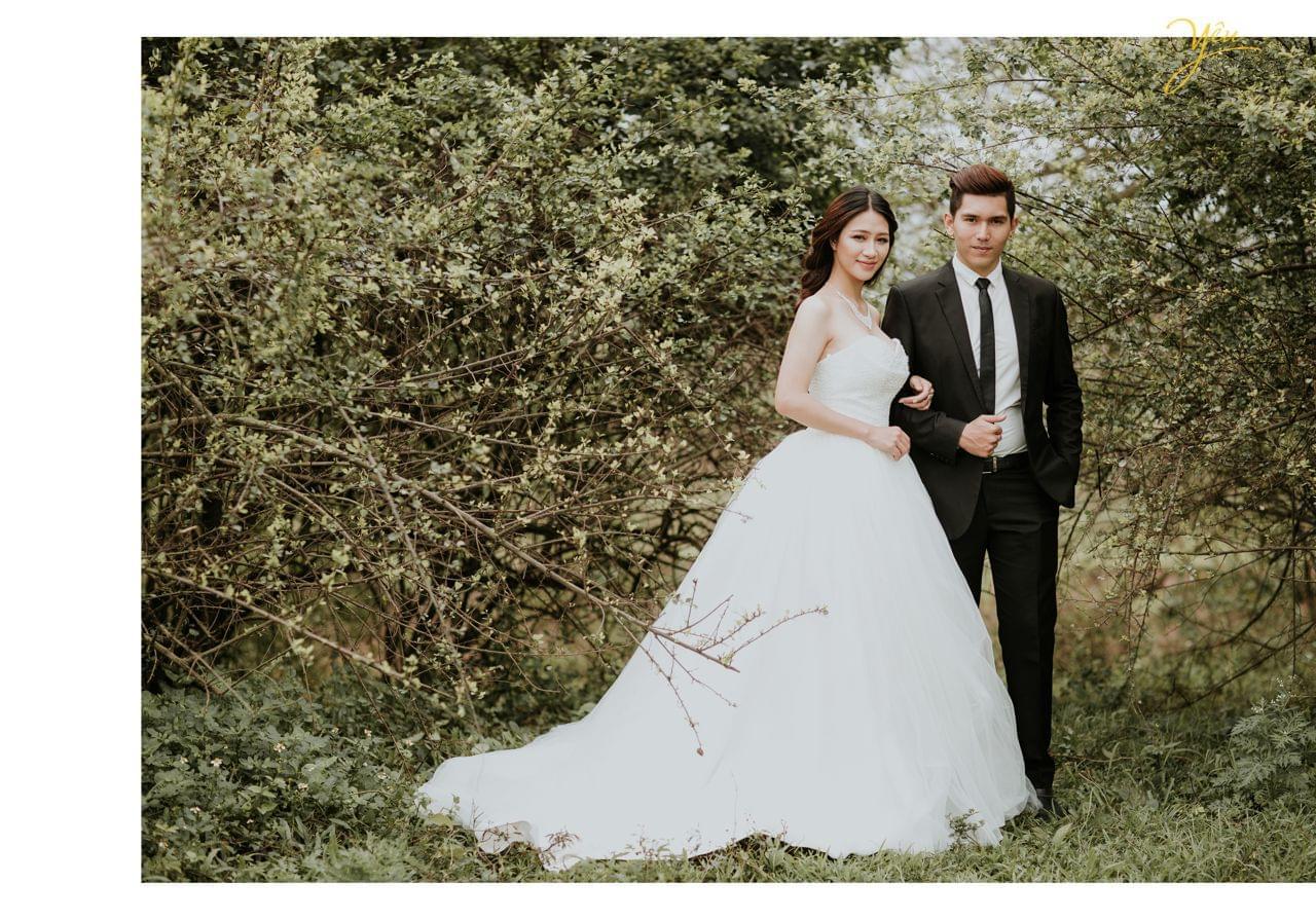 ảnh cưới ngoại cảnh cô dâu khoác tay chú rể đứng trong rừng