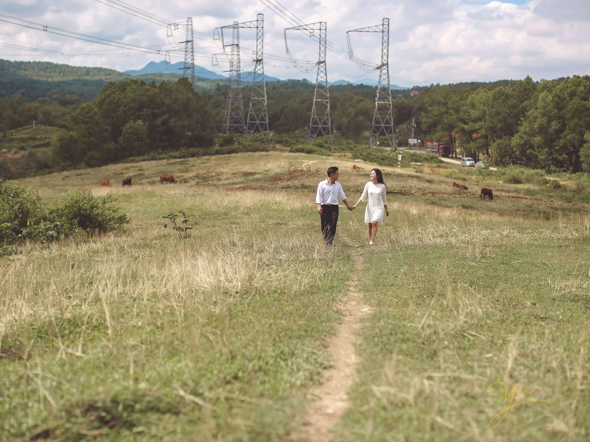 ảnh chụp từ xa cô dâu chú rể nắm tay nhau bước đi phía sau là núi đồi trập trùng
