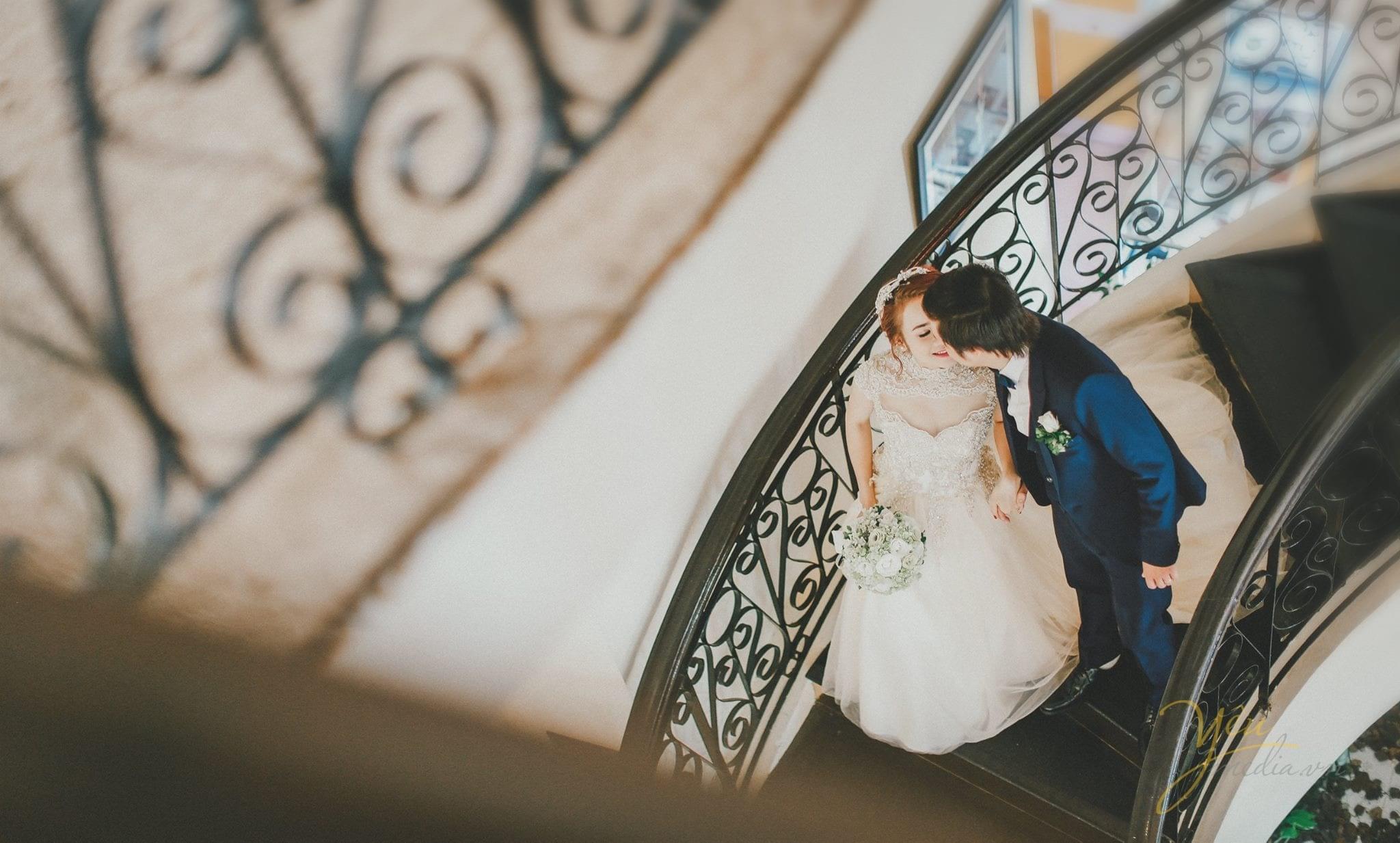 ảnh phóng sự cưới chụp từ xa cô dâu chú rể nắm tay nhau đi xuống cầu thang