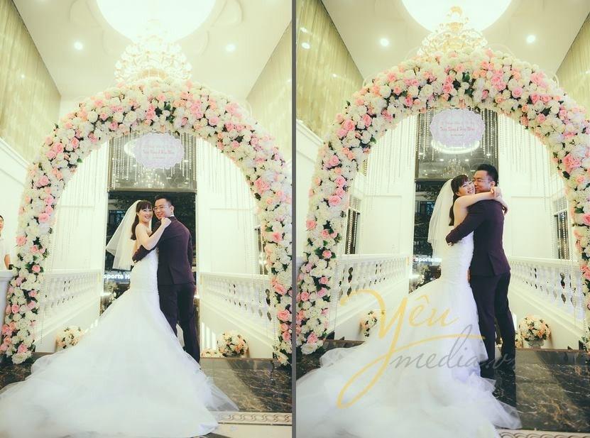cô dâu chú rể ôm nhau tại cổng hoa lễ cưới