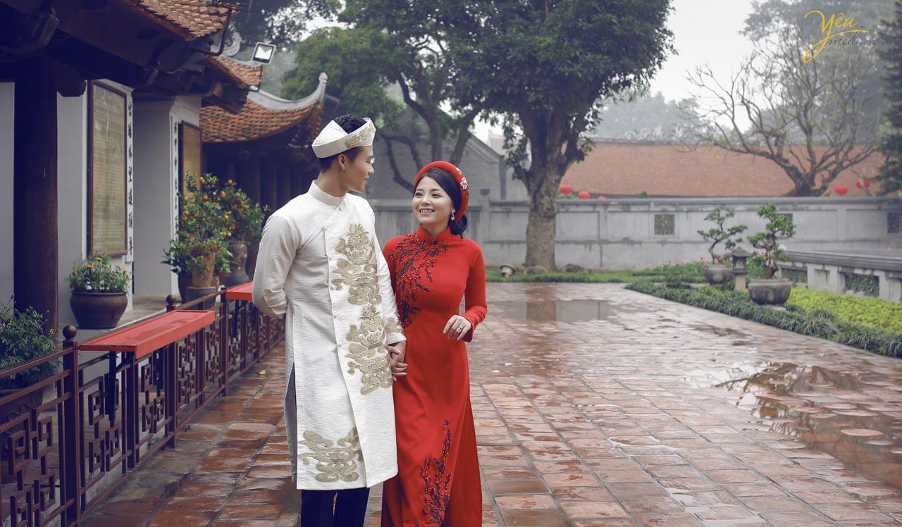 ảnh chụp cưới pre wedding áo dài đỏ cô dâu chú rể nắm tay nhau