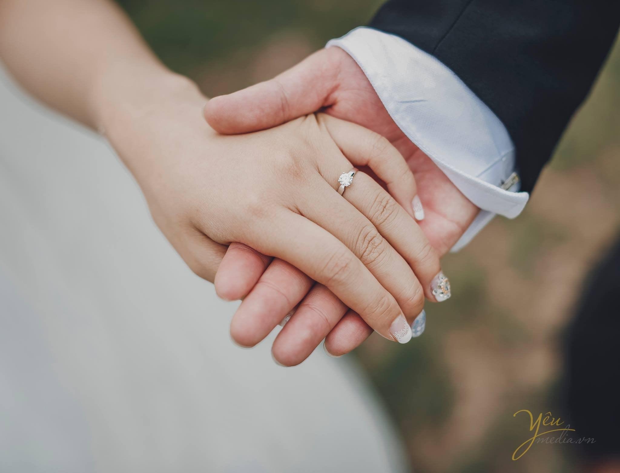 ảnh chụp tay chú rể và cô dâu cùng đeo nhẫn