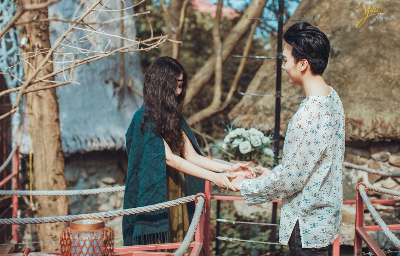 cô dâu chú rể nắm tay nhau trên cầu