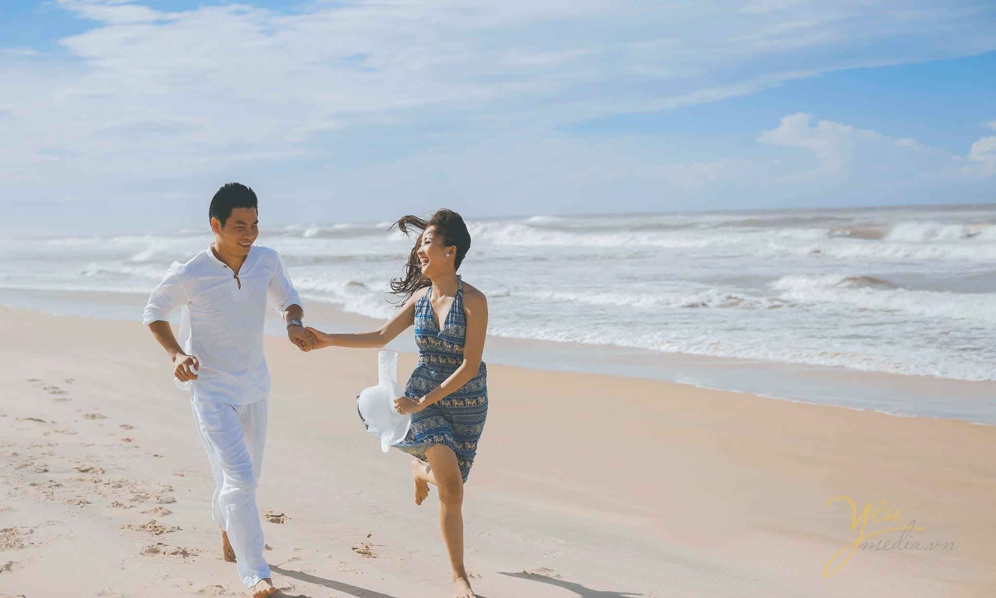 cô dâu chú rể nắm tay chạy trên cát bờ biển
