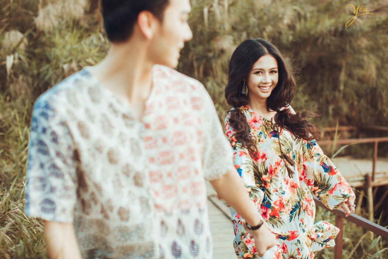 ảnh chụp qua vai chú rể cô dâu tươi cười chạy phía sau