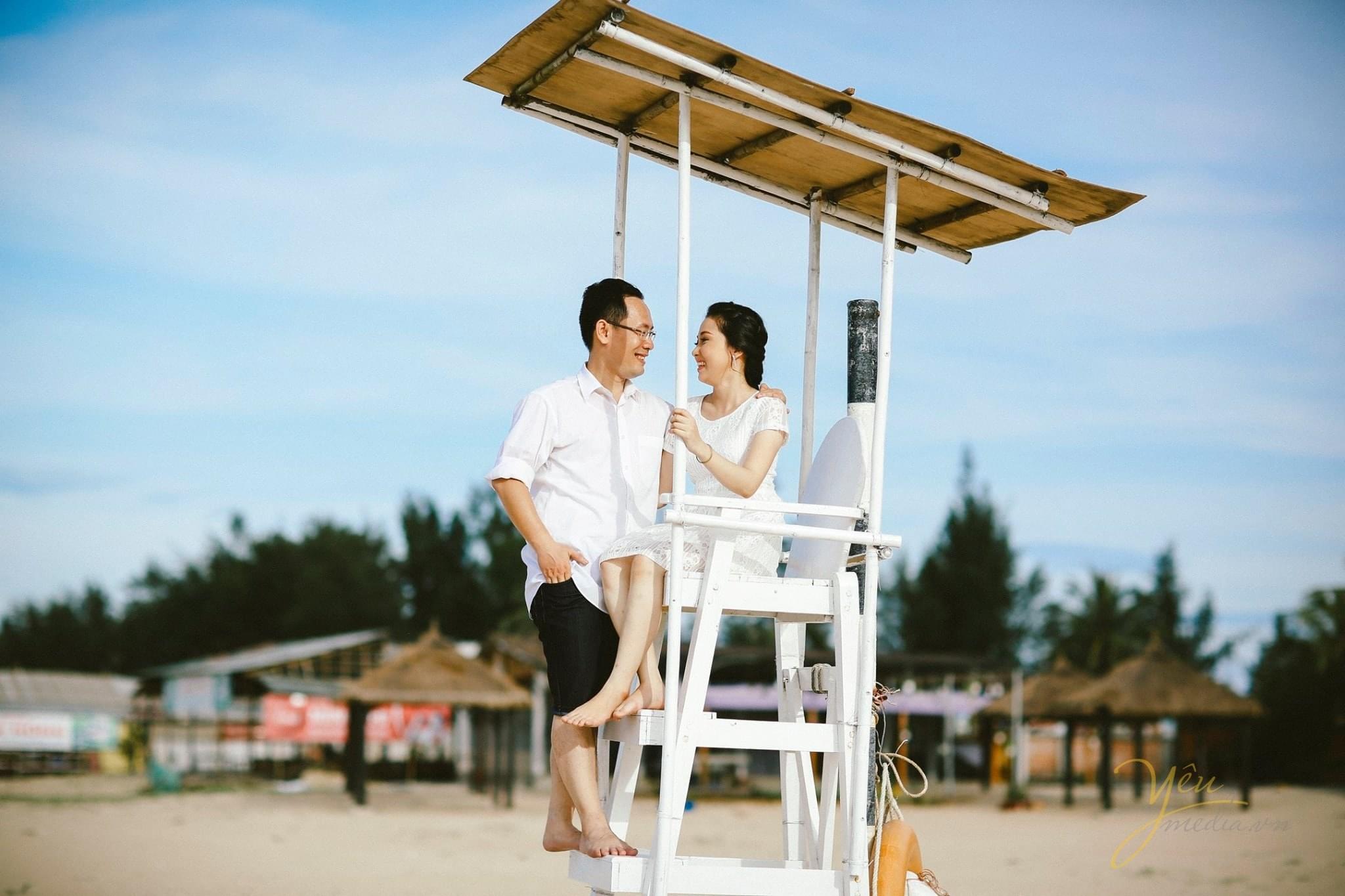 cô dâu chú rể ngồi trên chòi canh trên biển