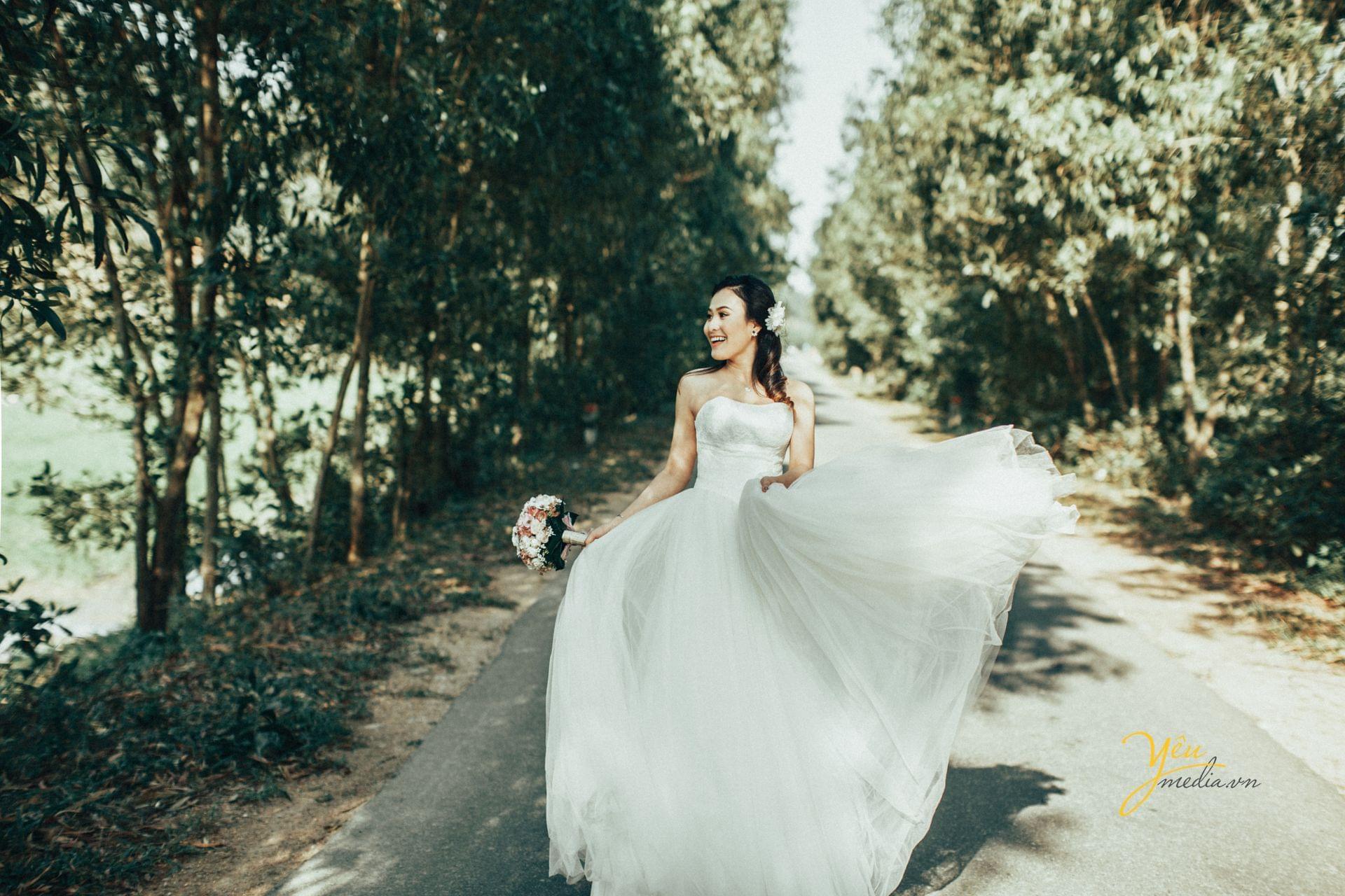 cô dâu tung tăng trong bộ váy cưới cười tươi trong nắng