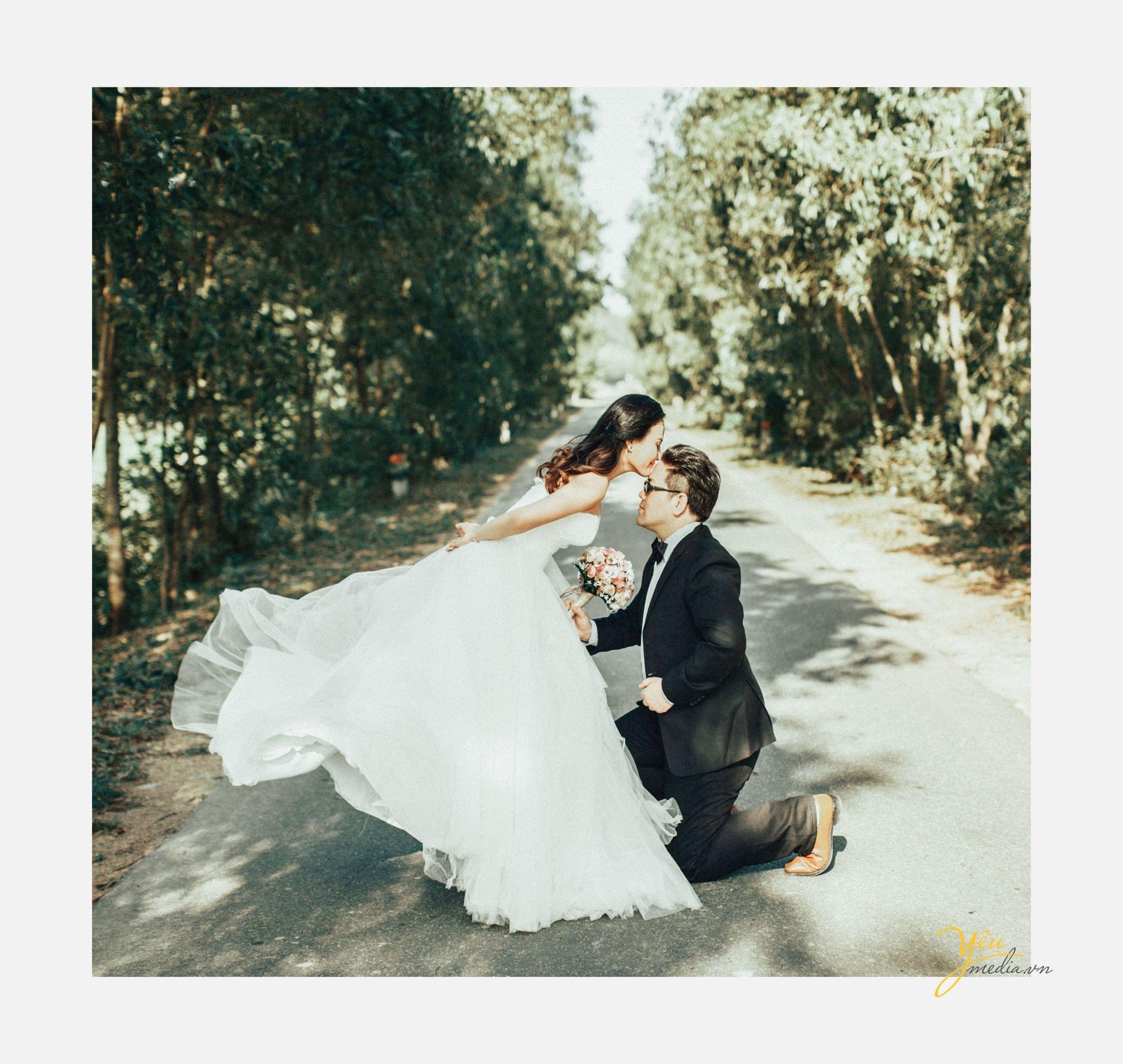 chú rể quỳ dưới chân cô dâu cô dâu hôn trán chú rể