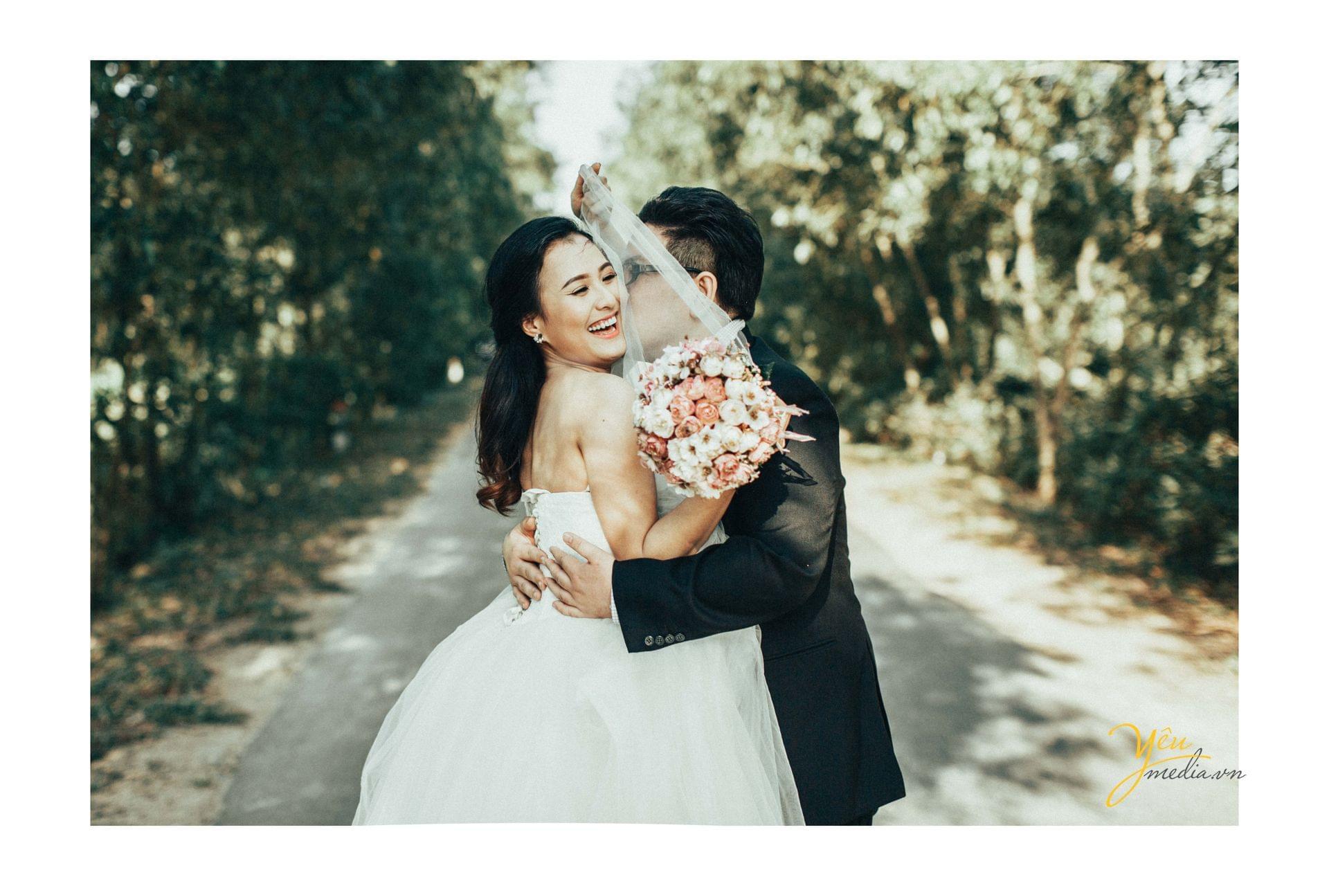 chú rể hôn má cô dâu cười hạnh phúc
