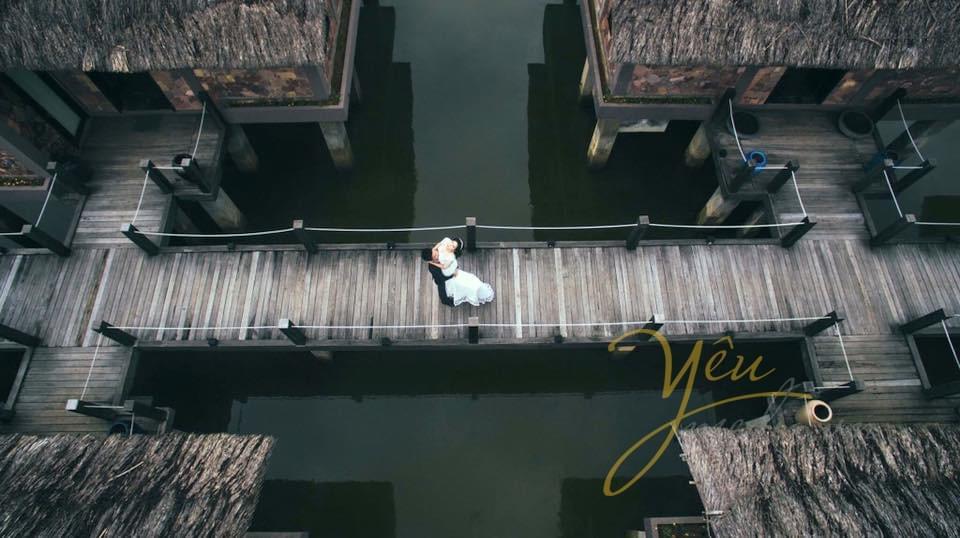 ảnh chú rể bế cô dâu giữa cầu chụp từ trên cao