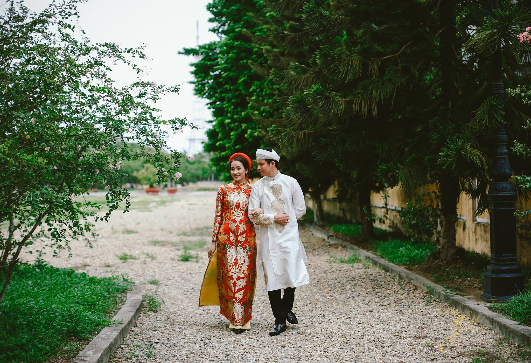 ảnh cưới áo dài cổ truyền cô dâu chú rể khoác tay nhau đi dọc đại nội huế