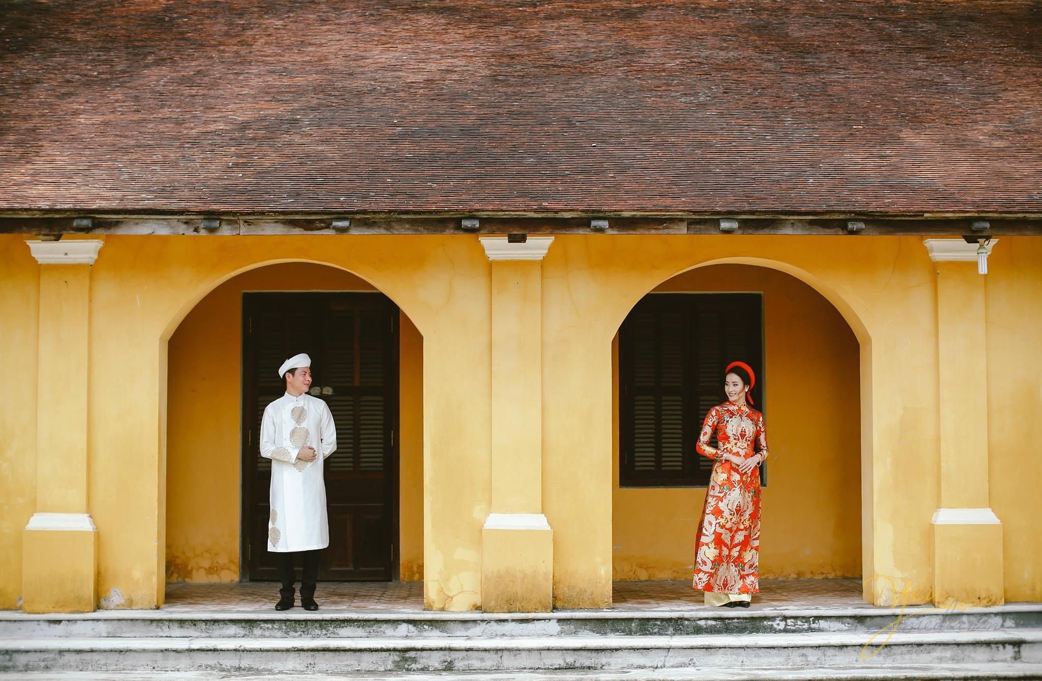 ảnh cưới trang phục áo dài cổ cô dâu chú rể đứng ở hiên nhà cổ