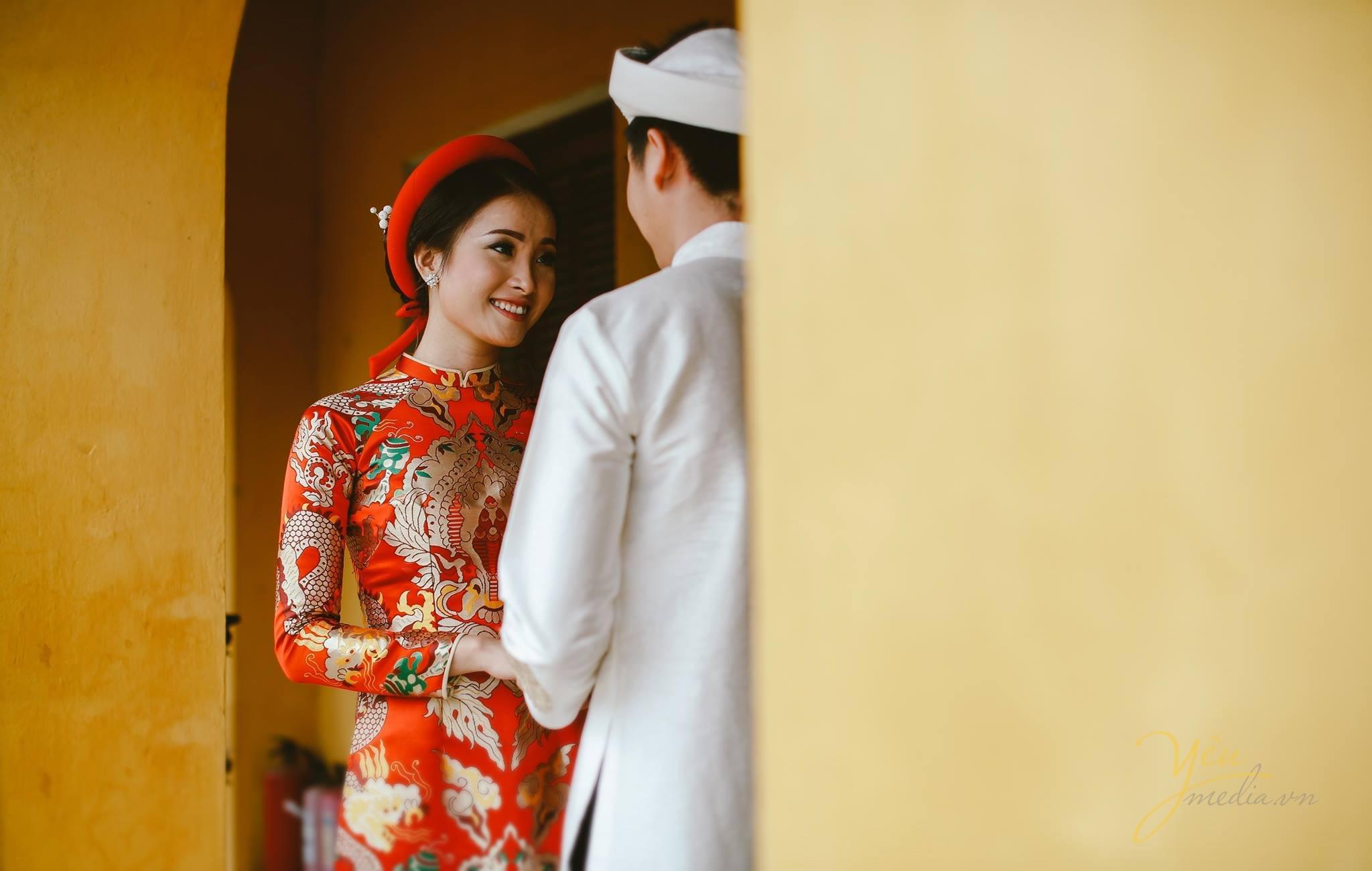 ảnh cưới áo dài gấm đỏ cô dâu chú rể nhìn nhau tình tứ