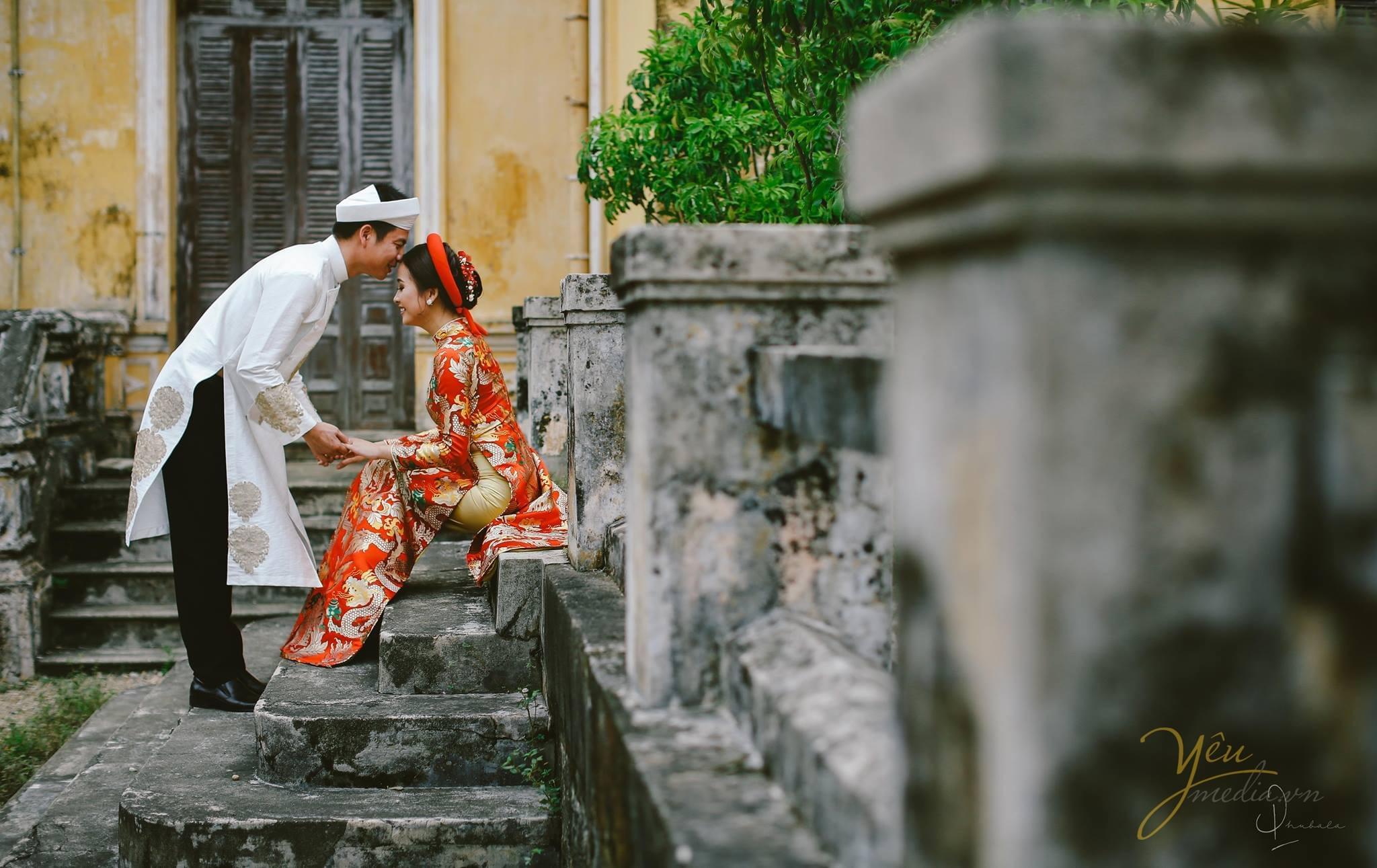ảnh cưới chú rể mặc áo dài cổ truyền hôn trán cô dâu