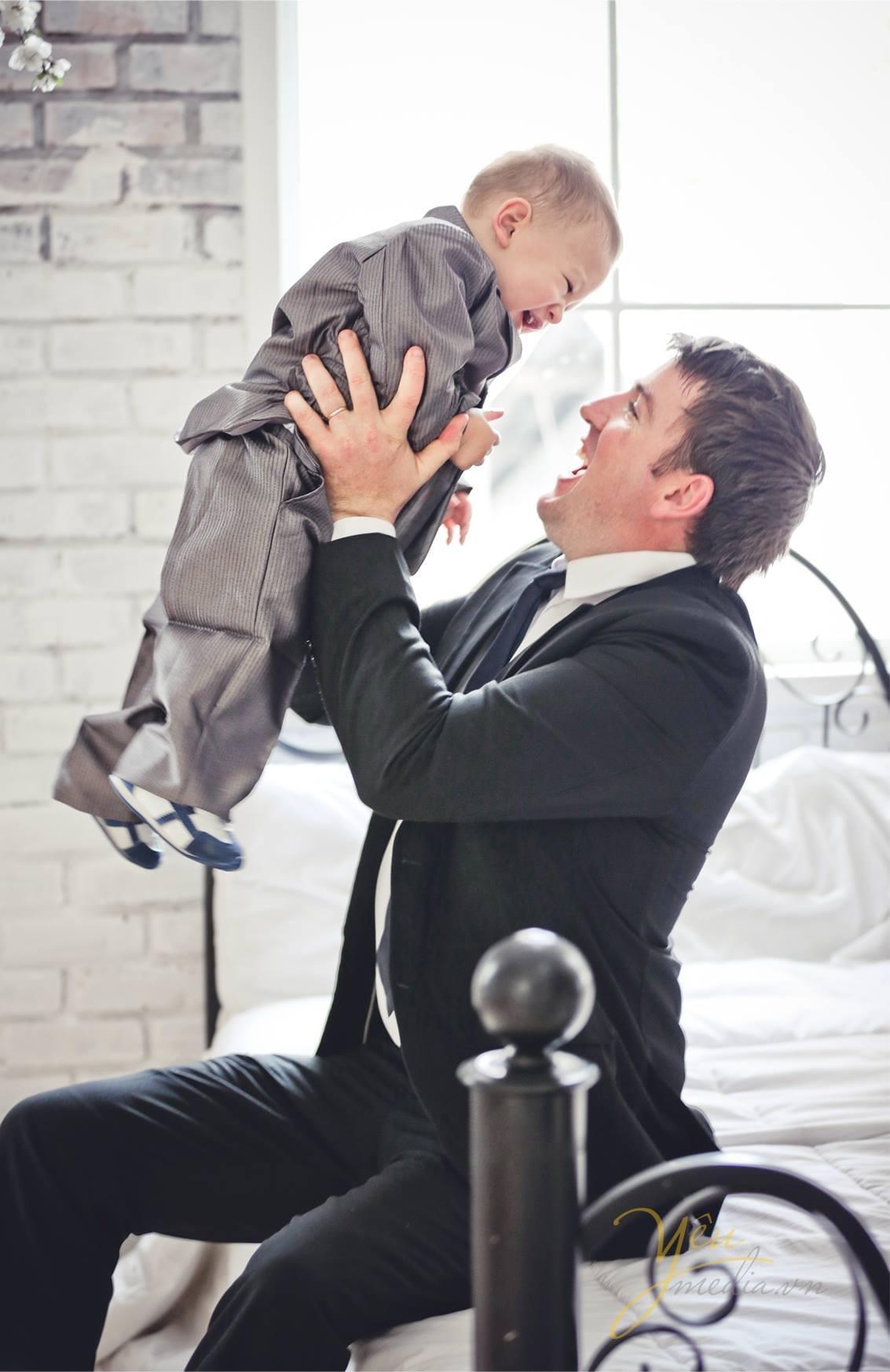 chụp ảnh bố bế em bé vui cười kỷ niệm sinh nhật