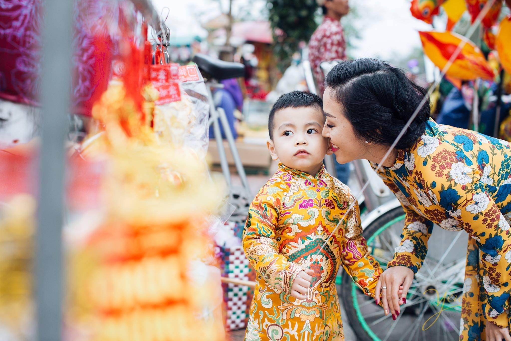 bé chụp ảnh áo dài tết với mẹ cạnh quầy bán lì xì, bóng bay