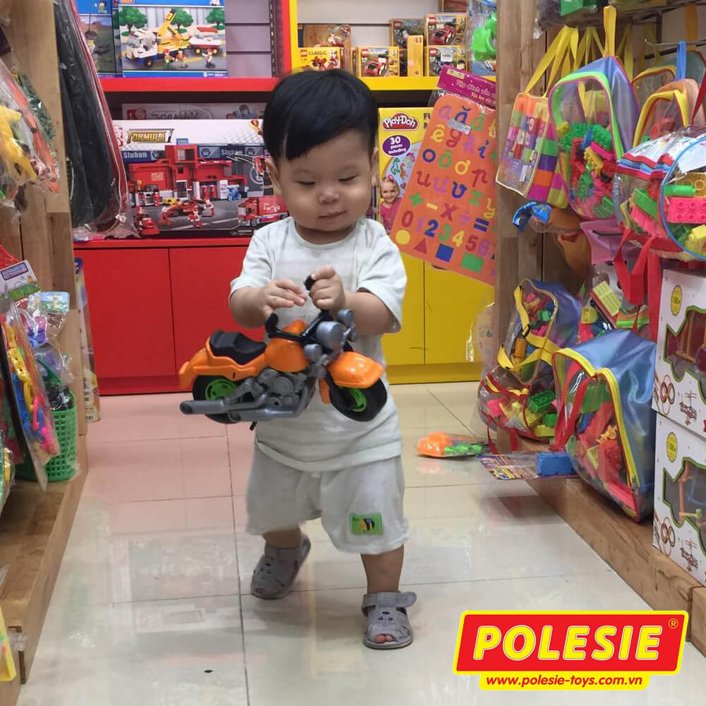 bé trai đang chơi xe mô tô đồ chơi Polesie Racing