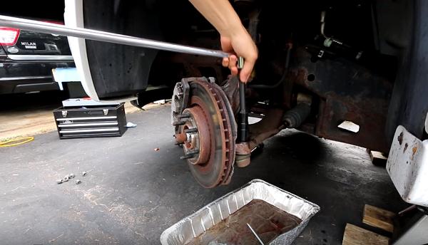 Sử dụng cờ lê để vặn bulông cố định trên phần khung giữ bánh xe