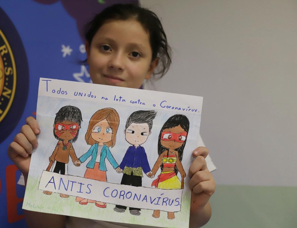 bé gái 9 tuổi ở Sao Paulo (Brazil), cầm bản vẽ của mình để ủng hộ cuộc chiến chống lại bệnh viêm phổi coronavirus mới ở Sao Paulo, Brazil, ngày 7 tháng 2 năm 2020. (Rahel Patrasso)
