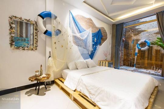 Phòng ngủ được trang trí mang đậm phong cách của biển với lưới đánh cá, phao bơi