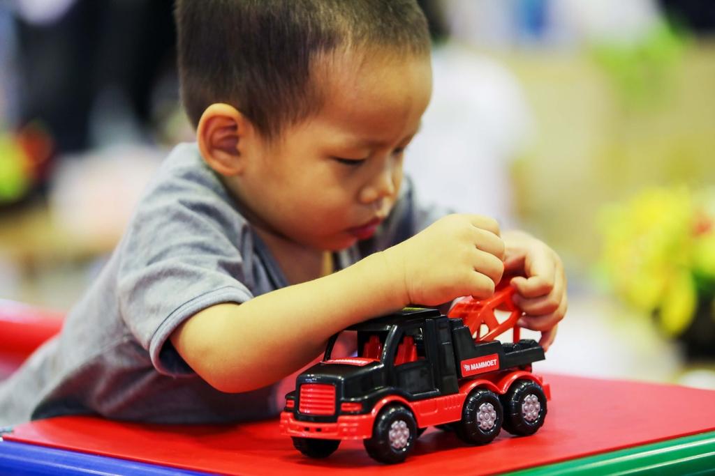 cậu bé kháu khỉnh đang nghịch ngợm xe đồ chơi Mammoet