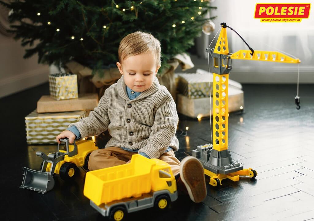 bé trai đang chơi bộ Cần cẩu tháp kèm 4 bánh đồ chơi