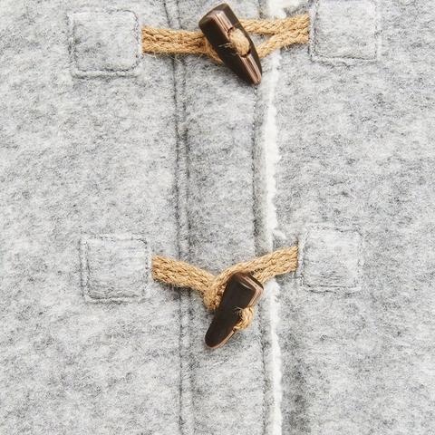 Ngoài khóa kéo, ở giữa áo còn có khuy sừng làm điệu