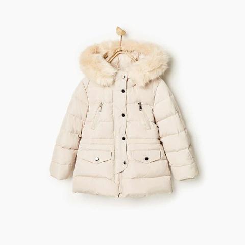 Áo khoác màu kem sành điệu, dáng áo chiết eo hơi xòe bên dưới