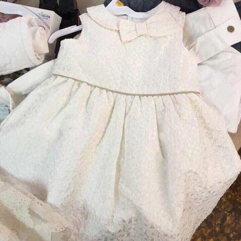 Váy màu trắng tinh khôi, phần cổ có nơ nổ bật
